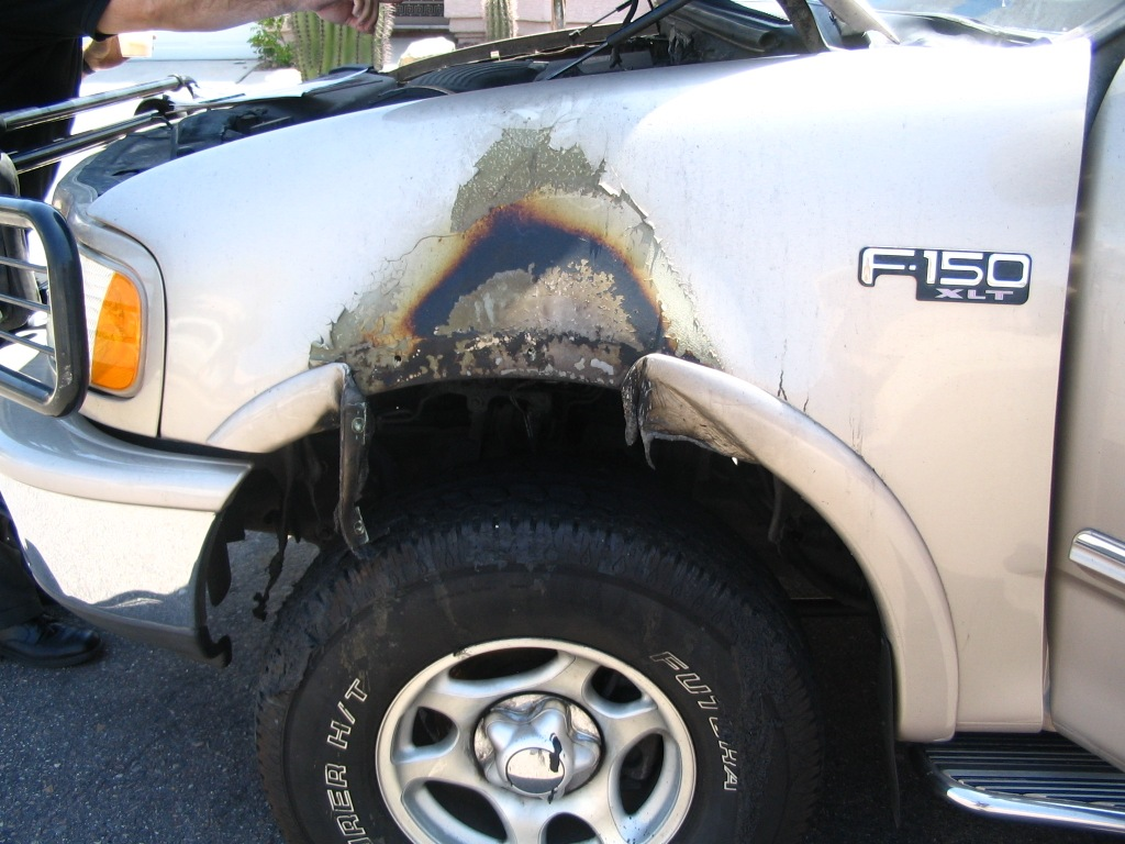 Inspecting burn pattern on driver side fender of 1997 Ford F-150 that caught fire while parked