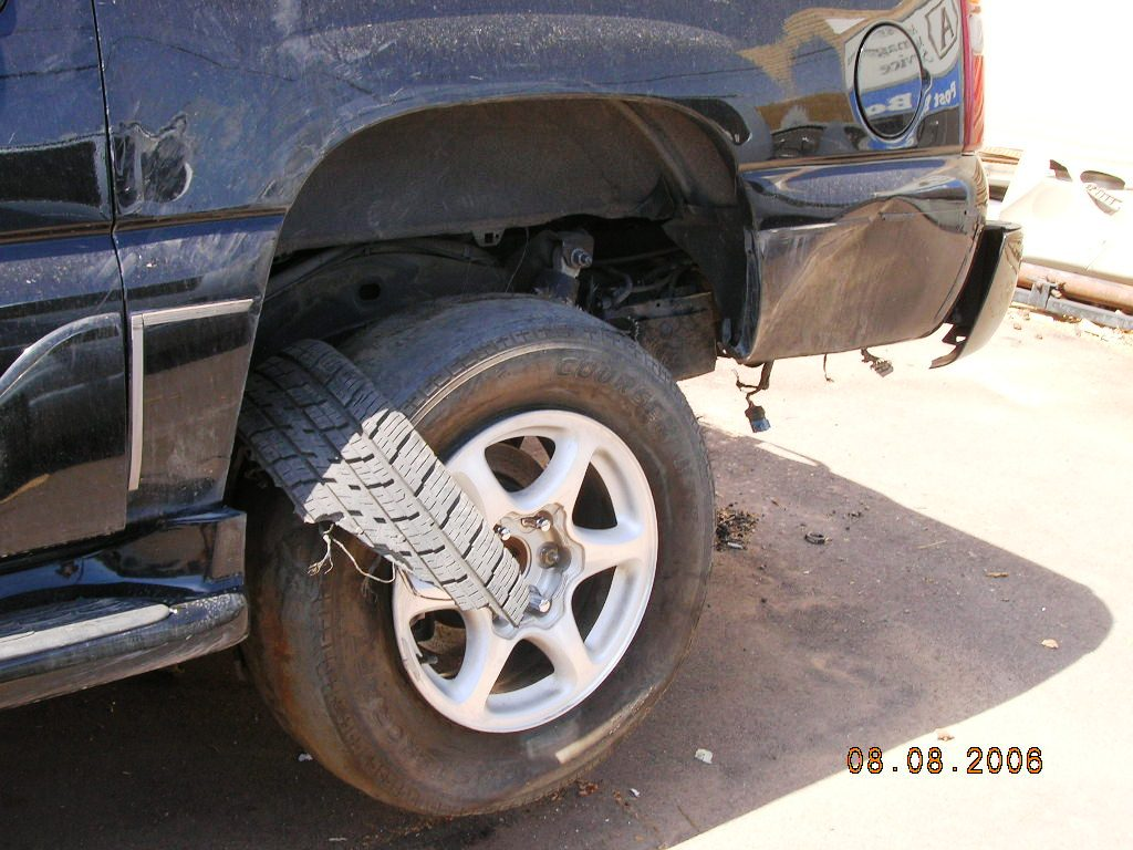 Inspecting failed rear tire of GMC Yukon Denali involved in rollover accident caused by tire failure