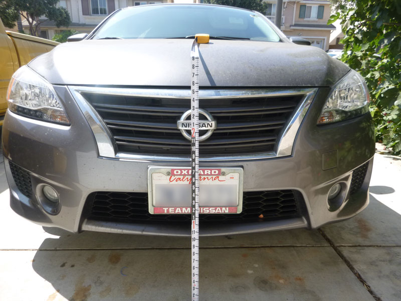 Inspecting and measuring front bumper of Nissan Sentra involved in rear-end accident