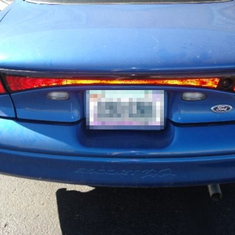 Inspecting rear end of Ford Escort involved in three vehicle rear end accident