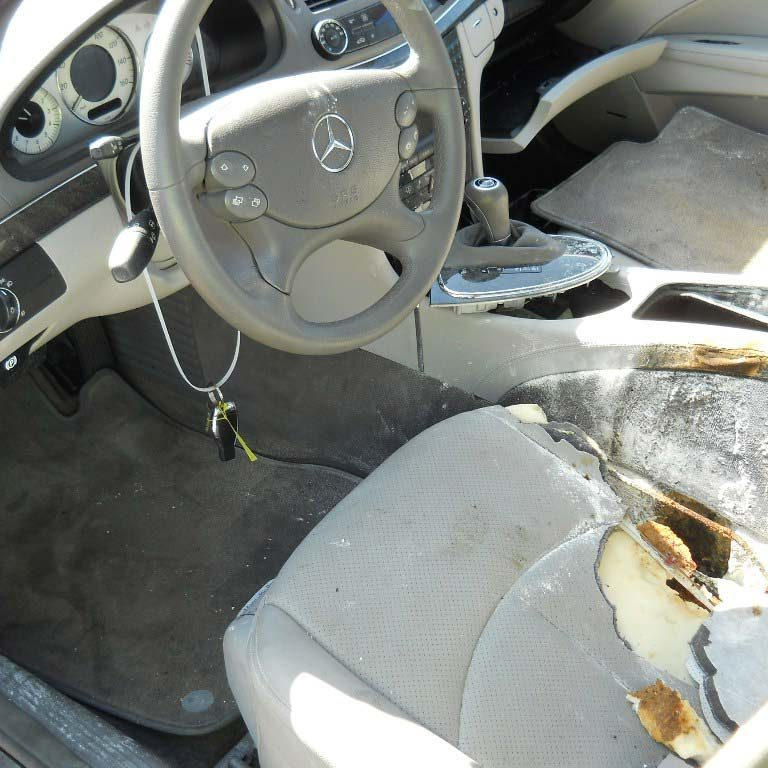 Driver side of Mercedes sedan showing burned driver seat