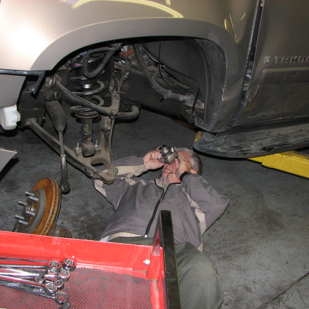 Inspecting front end suspension components of Chevrolet Tahoe